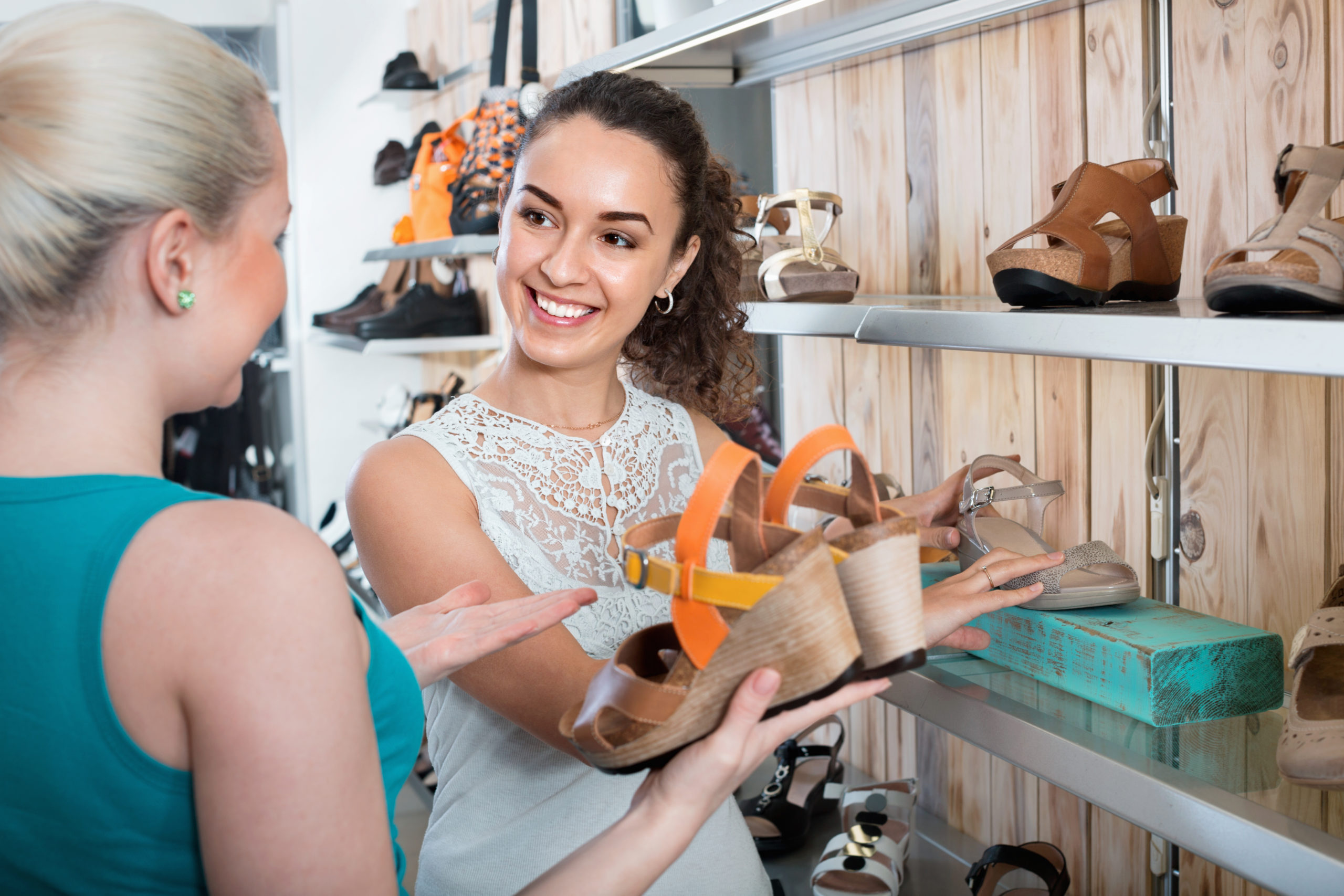 A sales assistant shows a customer some shoes