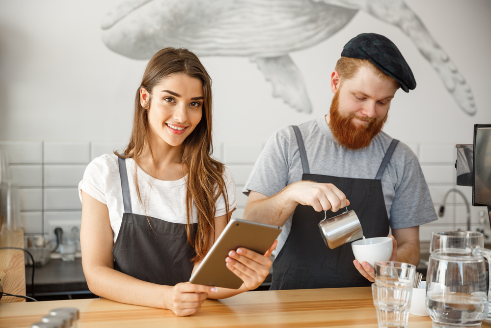 A woman and man work behind the counter of a coffee shop