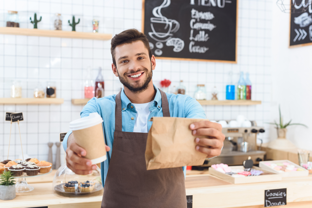 A cafe worker handing a coffee and paper bag to a customer