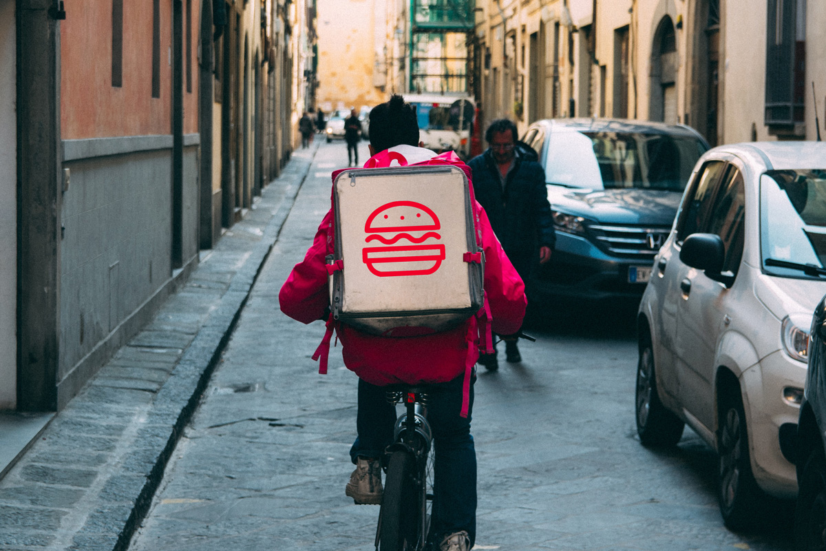 A photo of a delivery cyclist cycling down a street
