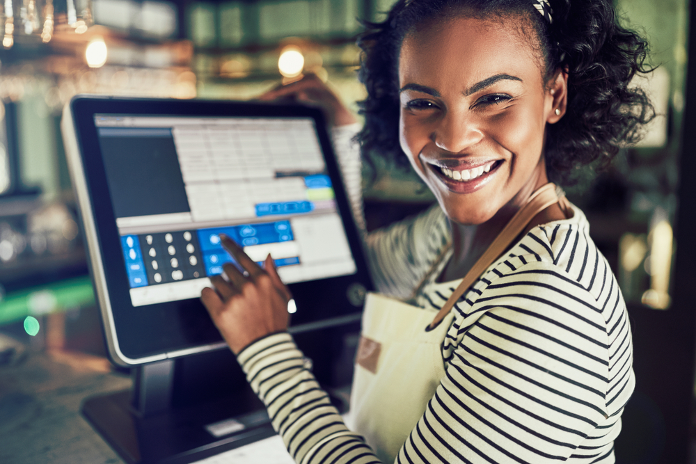 woman uses touch screen on restaurant POS terminal
