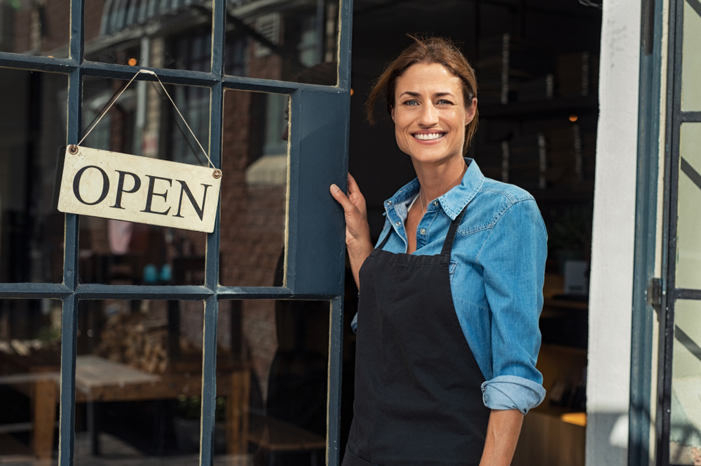 business owner standing next to open sign