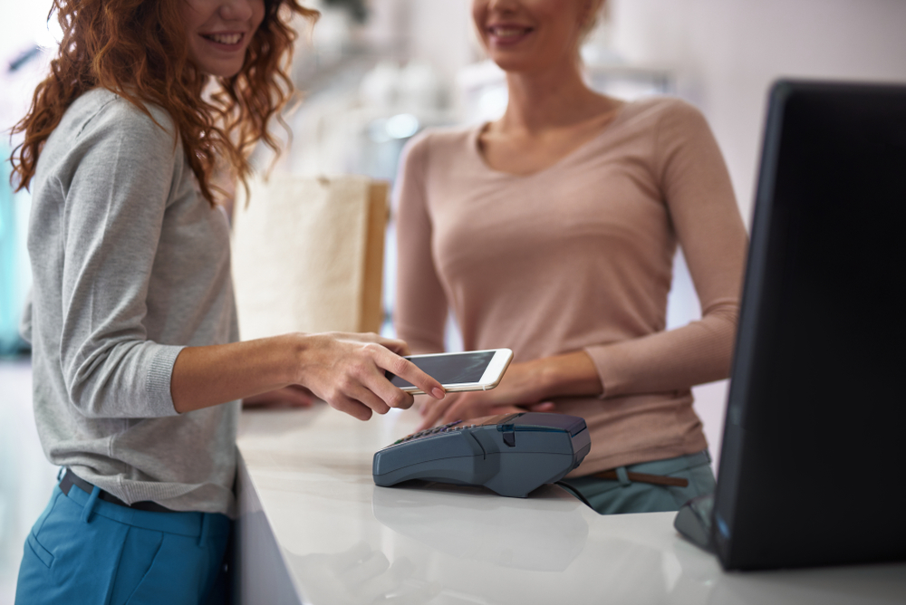 woman pays for salon appointment with contactless mobile payment on modern POS system