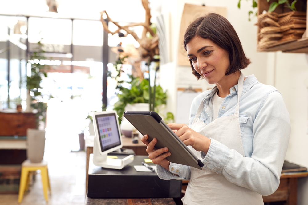 shop owner uses POS software on tablet for accounting