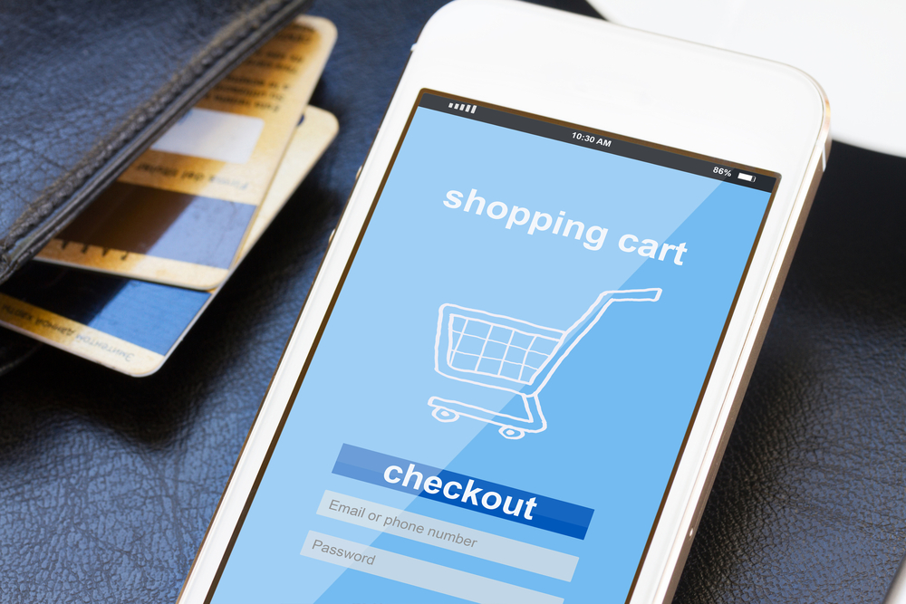 credit cards and phone displaying online shopping cart