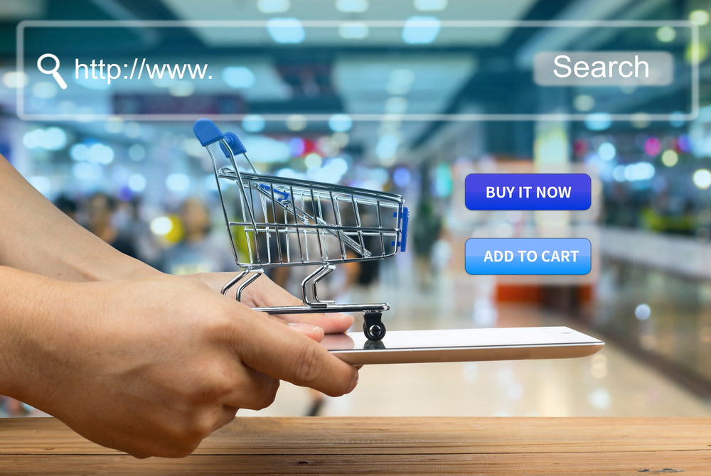 hand holds miniature shopping cart representing ecommerce