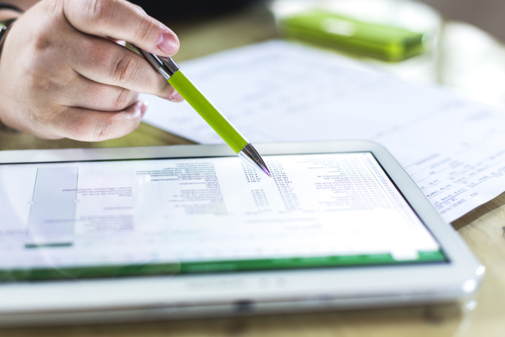 user consults Quickbooks software on tablet