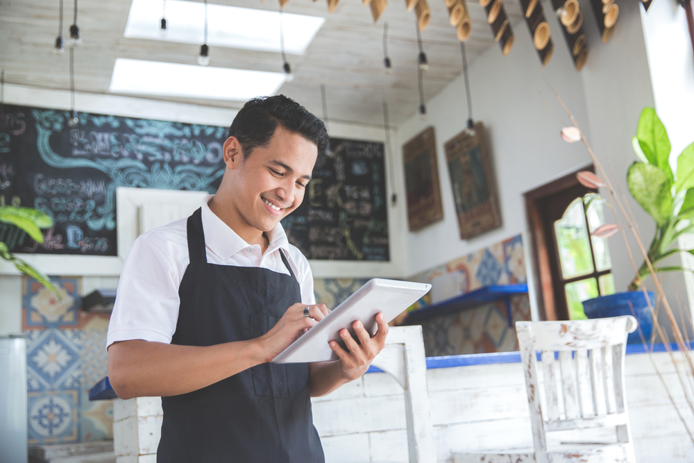 small business owner uses to POS on tablet to take order