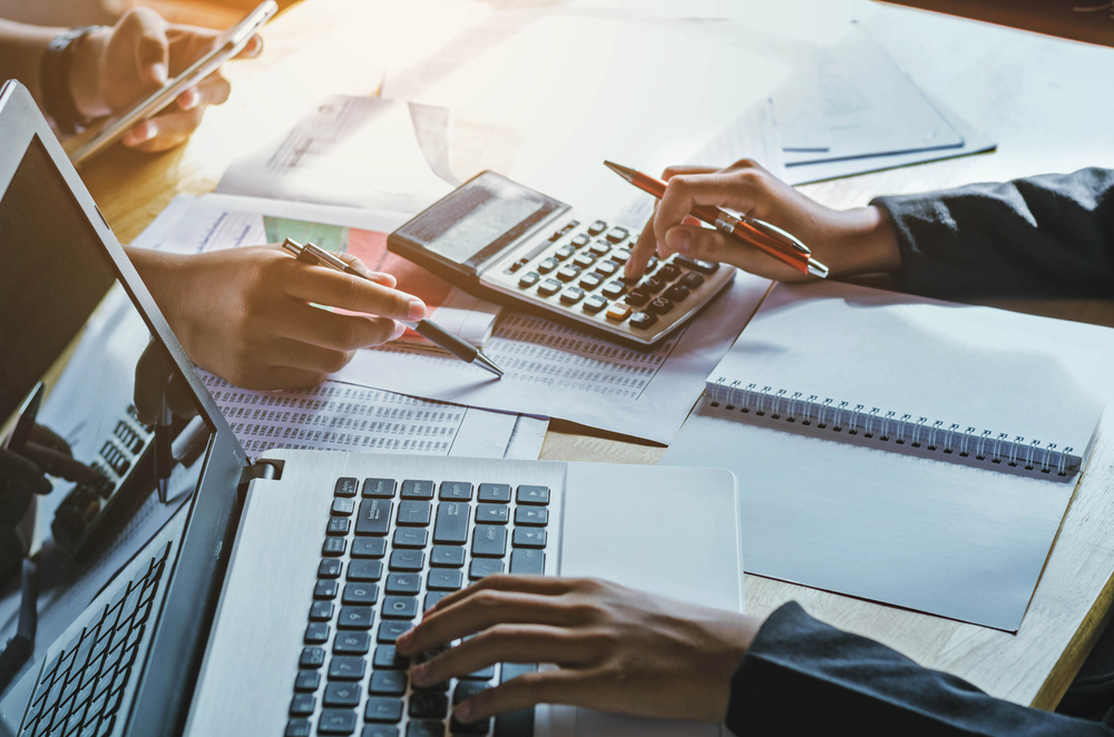 business owners use accounting software on laptop to balance budget