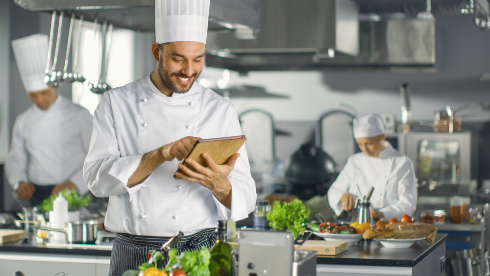 chef in kitchen uses tablet to access POS