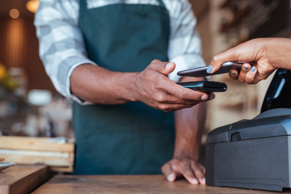 employee takes contactless payment from customer on POS equipment