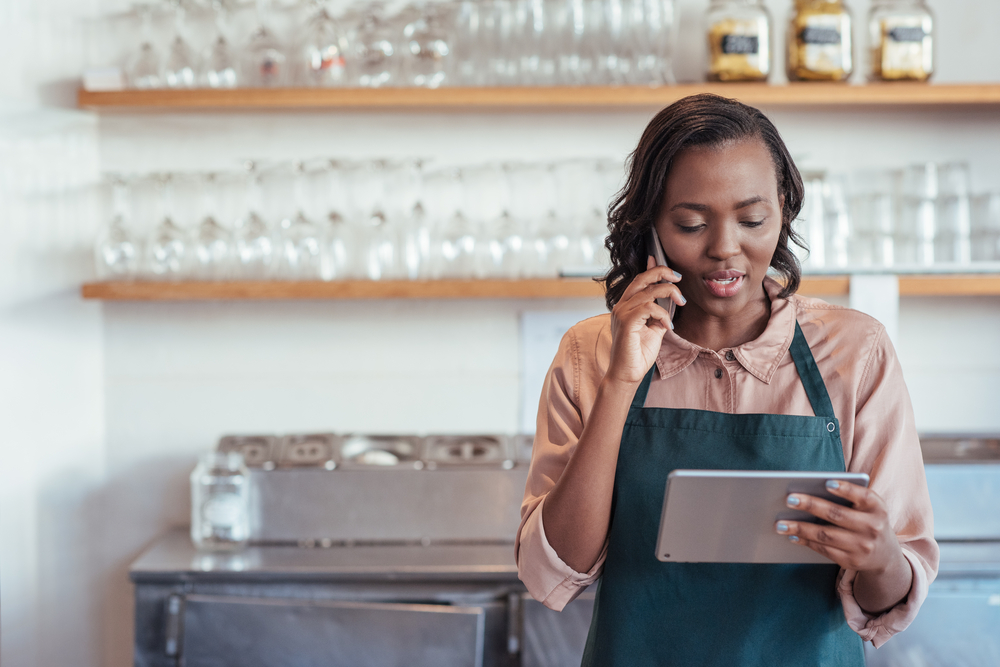 employee looks at pos tablet while on phone