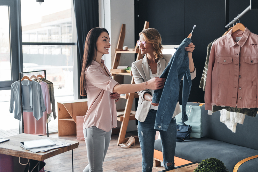 two women look at jacket in boutique