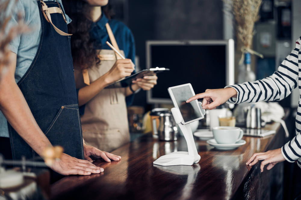 employees and customer at cafe use tablet pos to complete sale