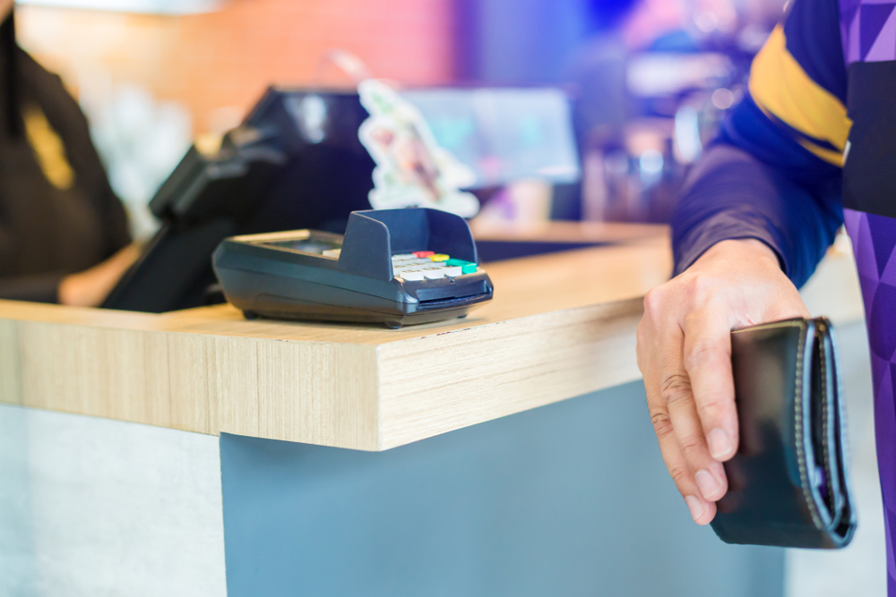 man holding wallet prepares to pay at point of sale