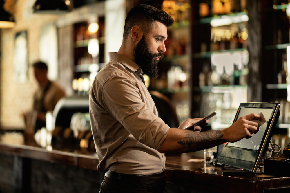 employee at bar uses point of sale system terminal