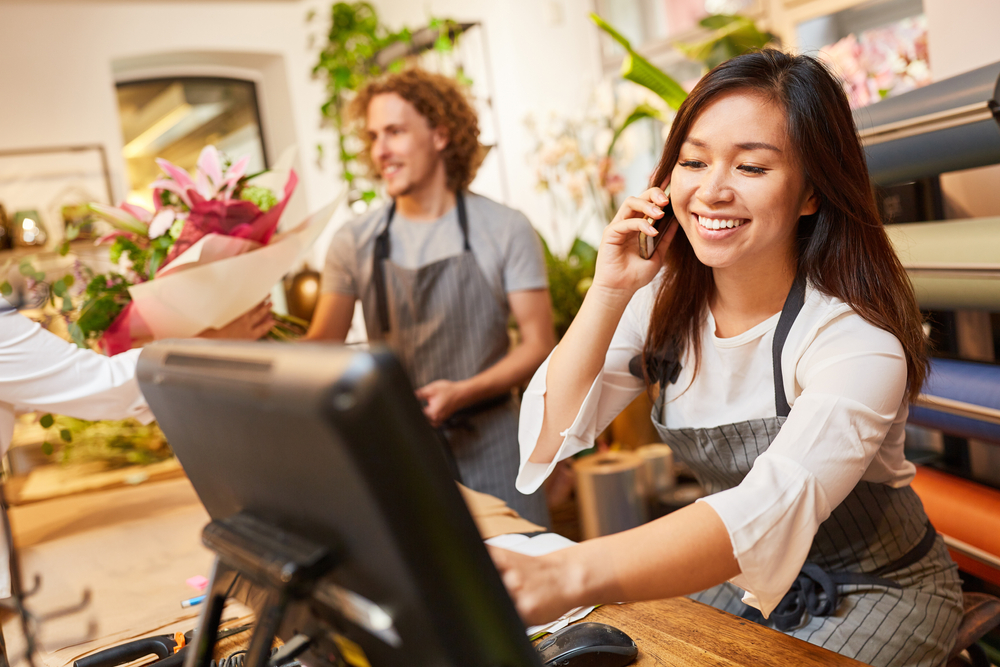 woman in shop takes phone order on POS system