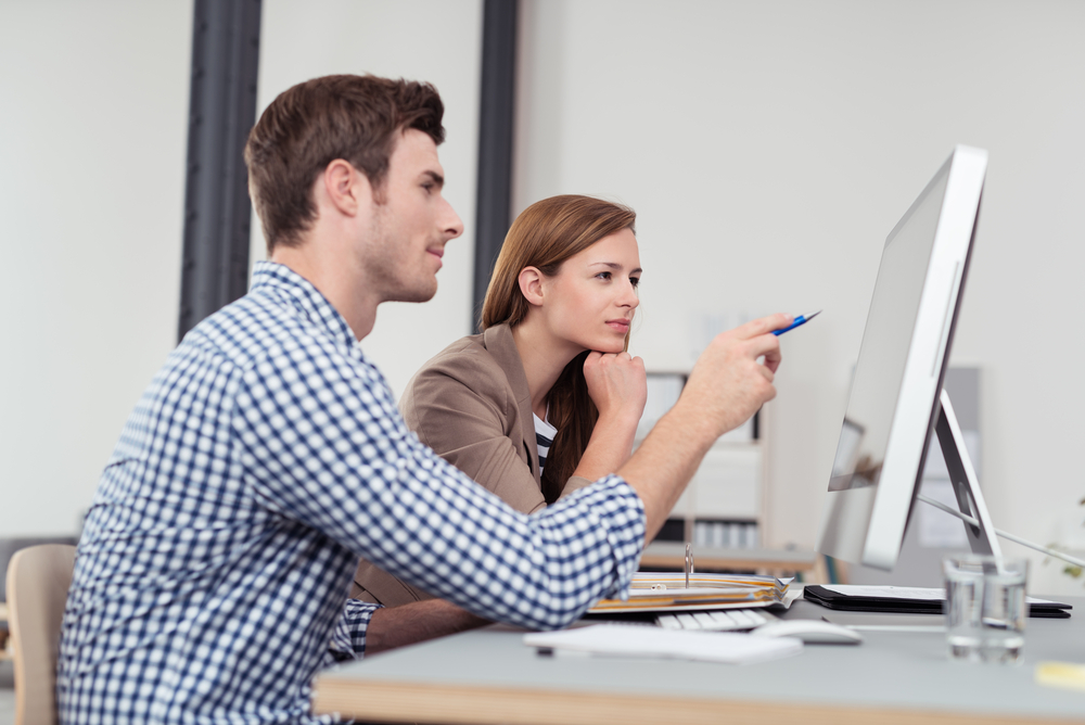 two computer users examine data on large monitor