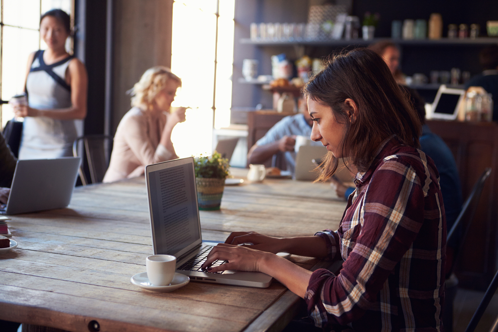 woman sits in coffee shop and types on laptop