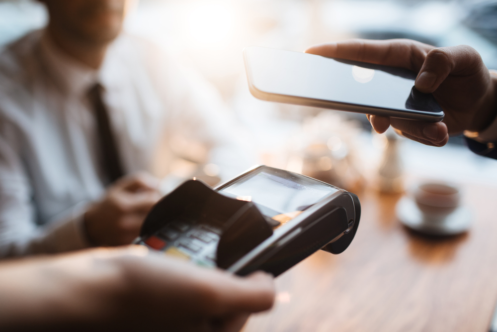customer makes a contactless payment with phone