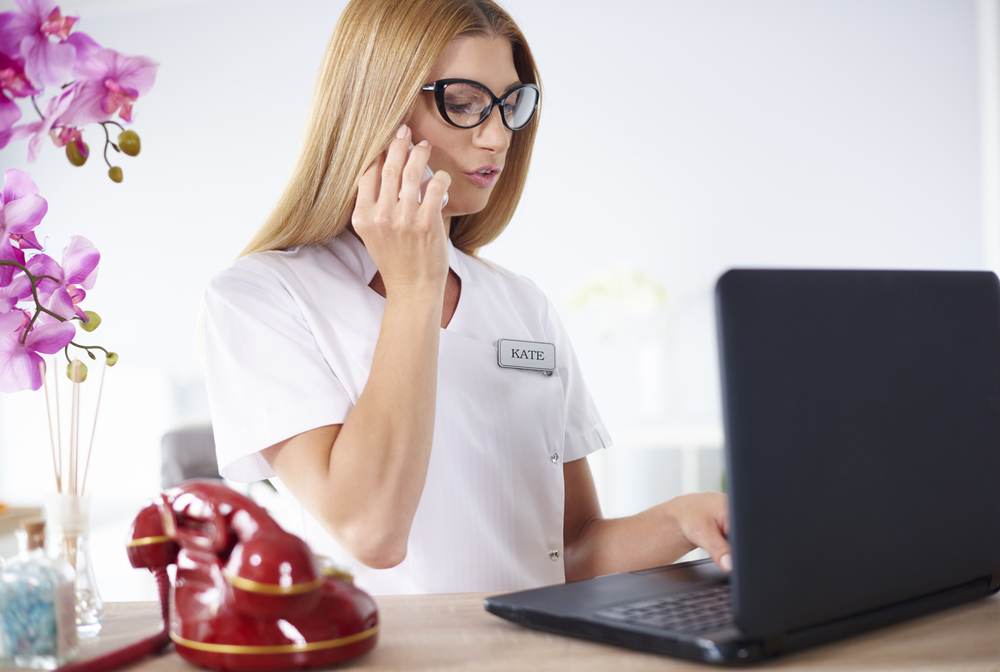 spa owner talks on phone while working on laptop