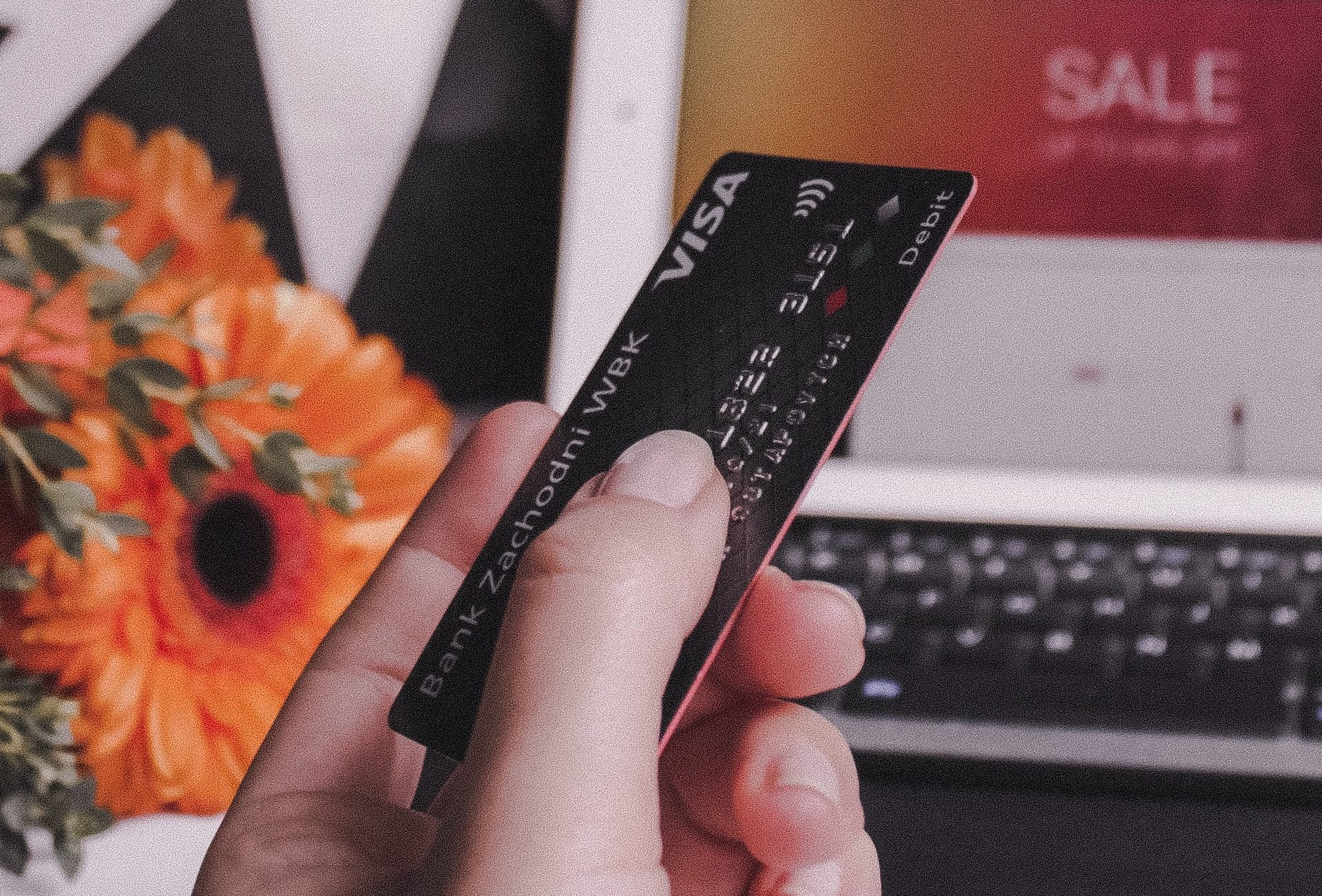 A hand holding a credit card as someone makes an online purchase