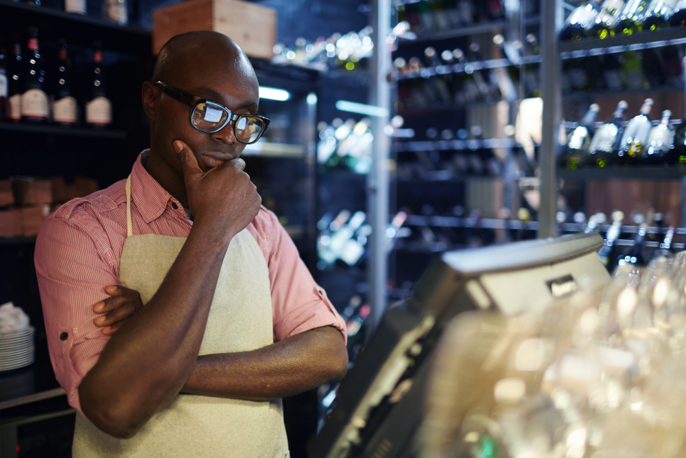 employee in restaurant looks at pos terminal