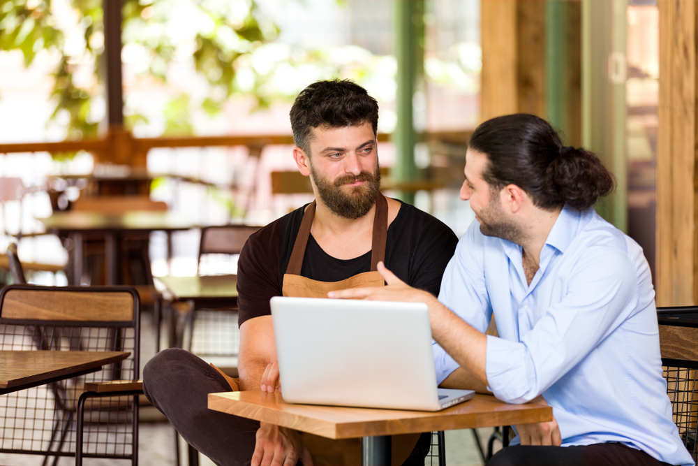 bar owners look at POS data on laptop