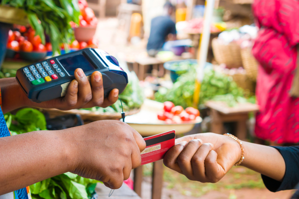 customer hands credit card to employee at market