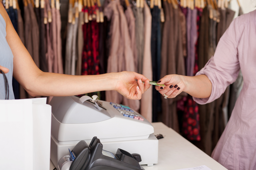 shopper gives credit card to cashier in clothing shop