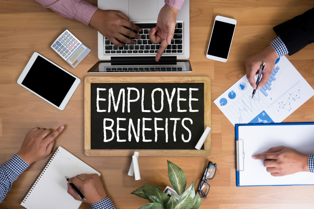 """employees sit at table around chalkboard that reads """"employee benefits"""""""