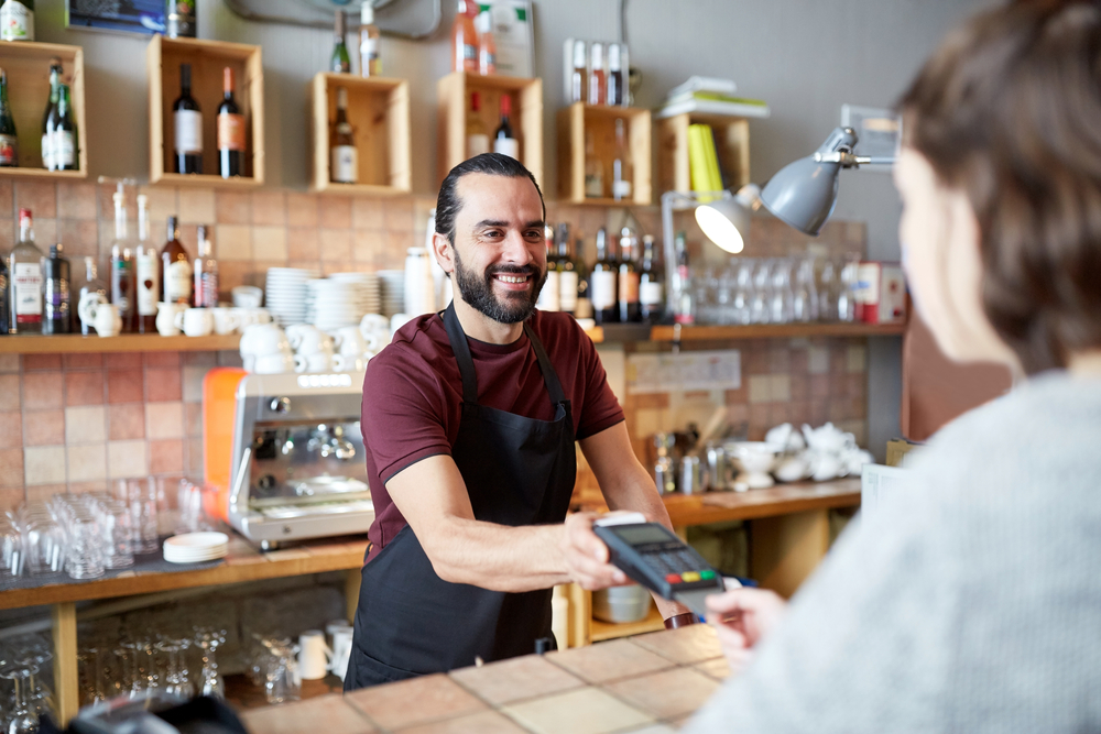 employee at cafe accepts credit card from customer