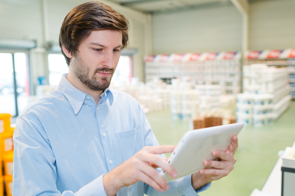man uses a tablet to track inventory in warehouse