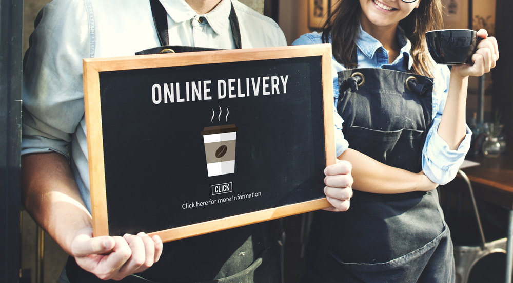 A cafe employee holds a sign saying 'online ordering'
