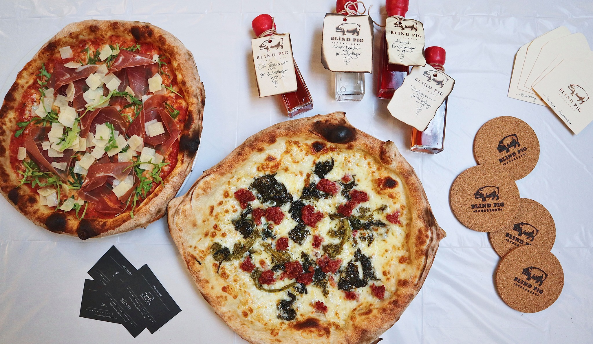 An image of two pizzas and some drinks