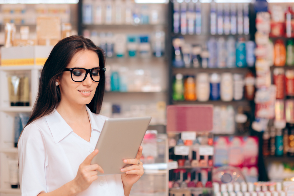 employee in beauty shop uses tablet to track inventory