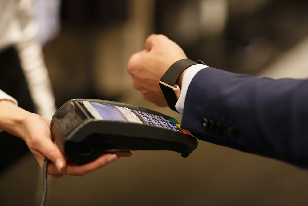 man uses smartwatch with pos to complete transaction