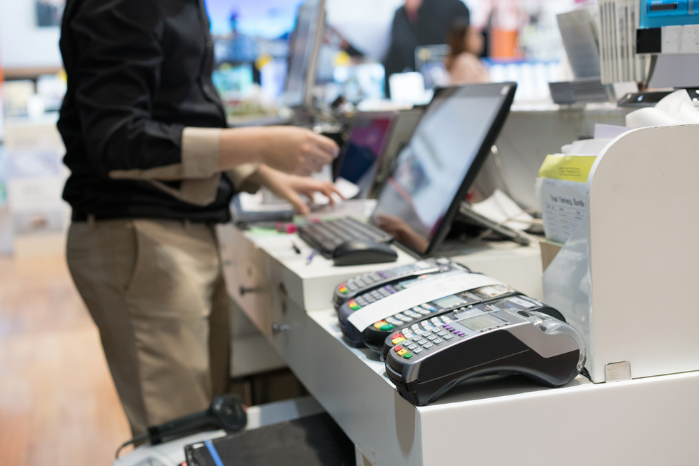 employee runs payments at a point of sale terminal