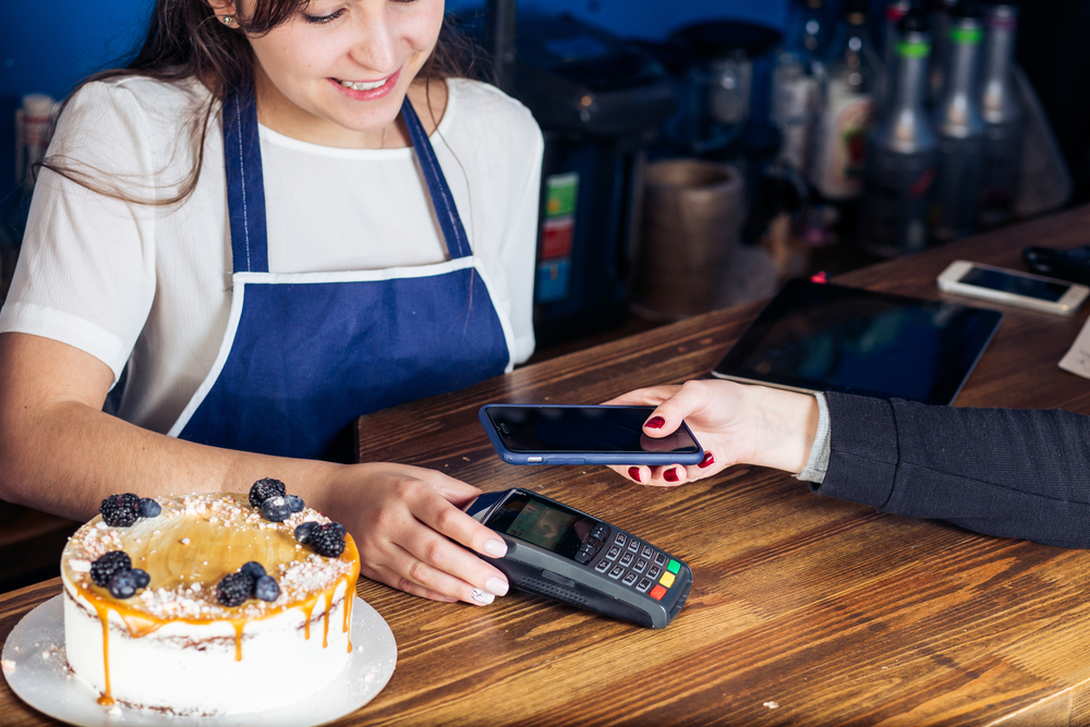 cafe employee uses pos terminal to accept contactless payment on customer's smartphone