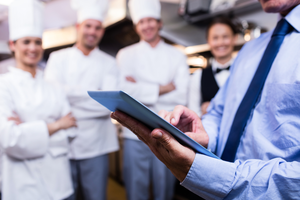 man in suit and tie uses a tablet pos in kitchen while chefs and waiters look on in background