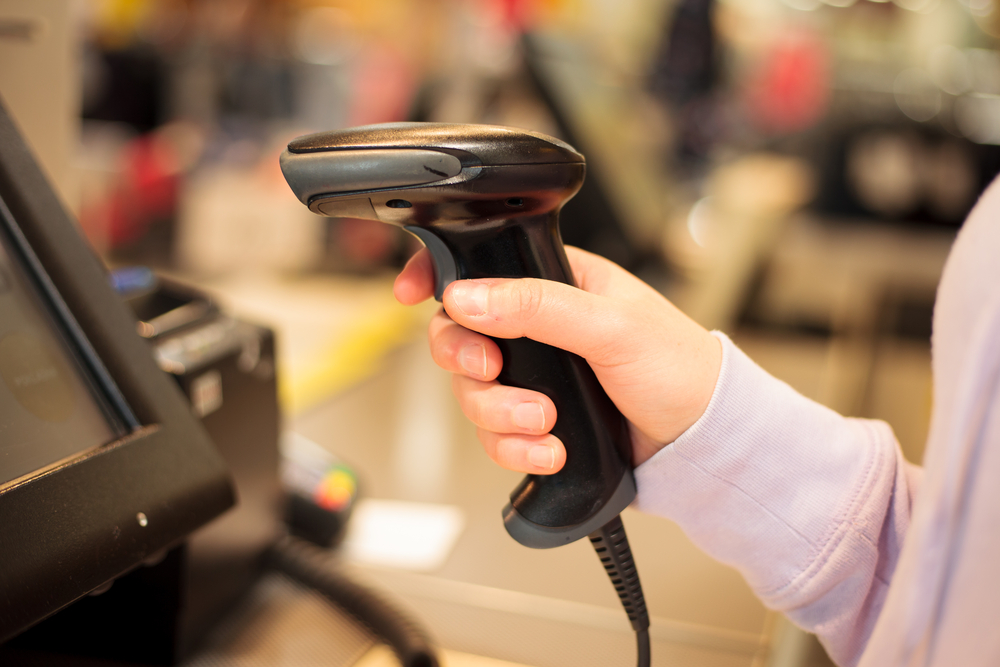 employee uses pos scanner to complete purchase transaction