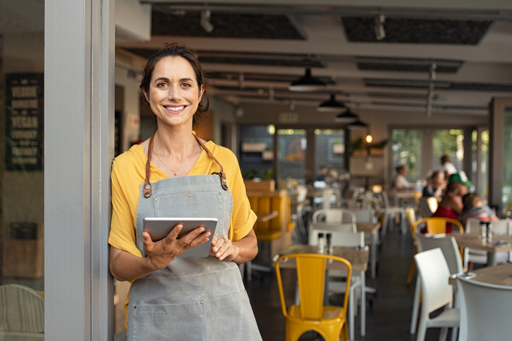 business owner wearing apron holds ipad and smiles
