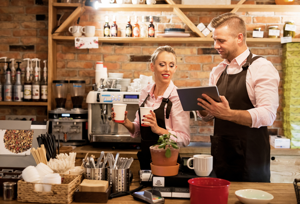 two cafe employees stand and examine a ipad pos
