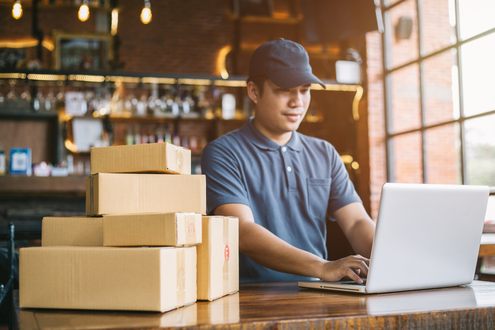 store employee preparing to ship boxes of purchases