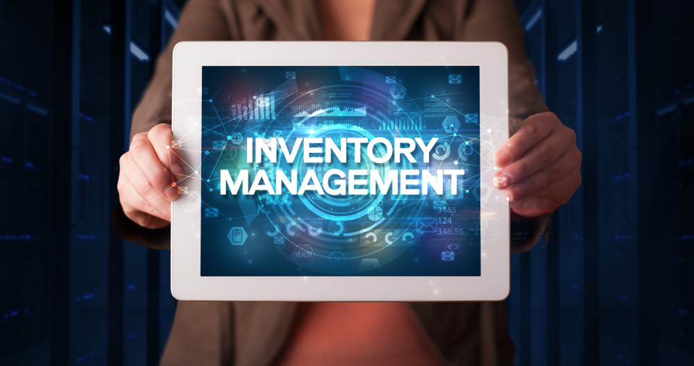 """hands hold a tablet displaying the words """"inventory solution"""" on screen"""