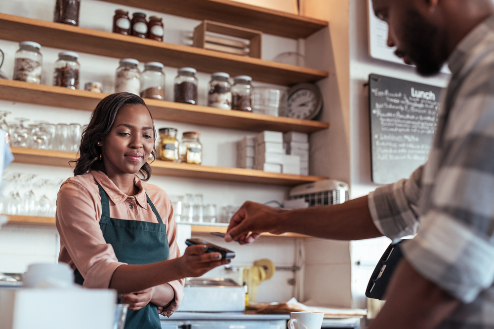 employee in shop uses pos system equipment to help customer complete a transaction
