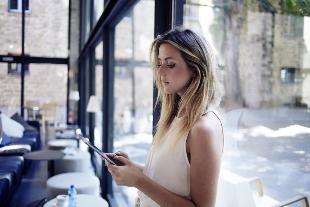 woman uses iPad with pos system in restaurant
