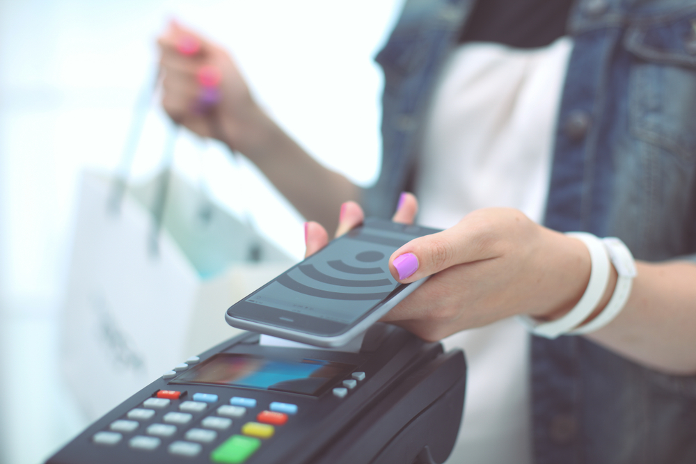 customer makes contactless payment with phone