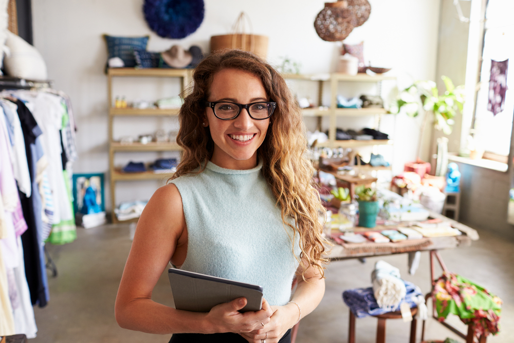 small business shop owner holds ipad with point of sale system