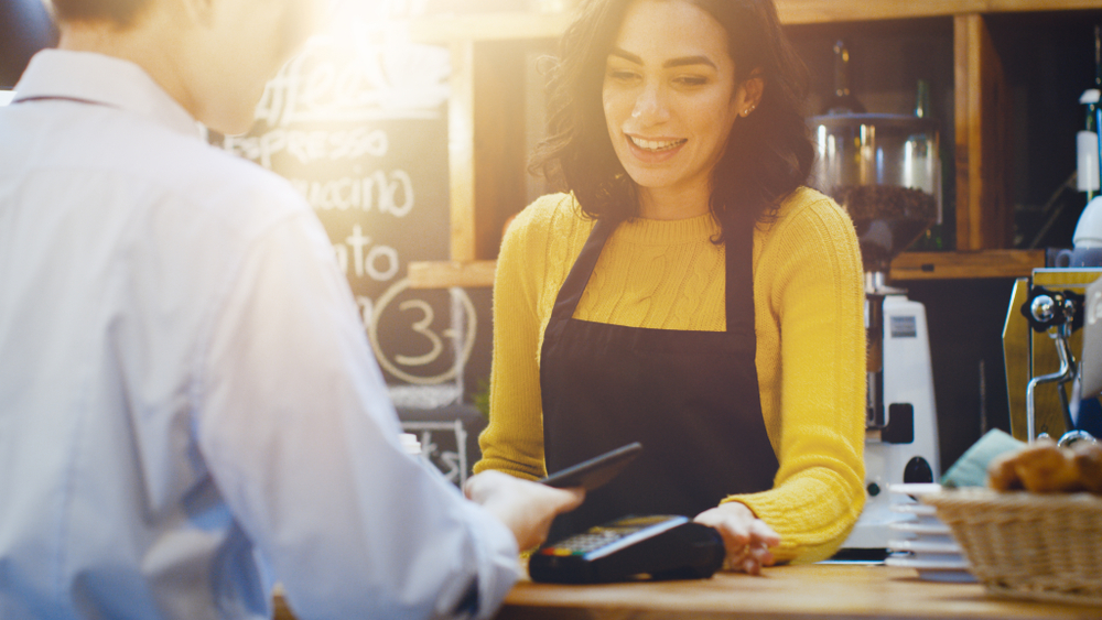 employee accepts contactless payment via pos